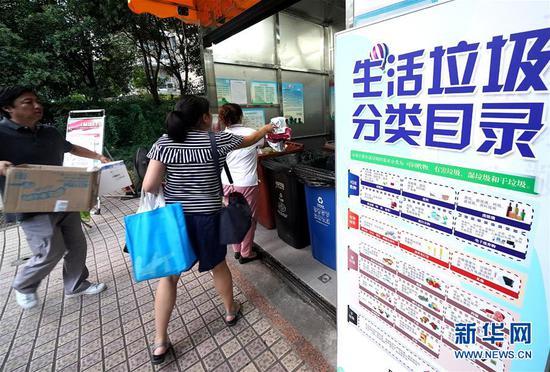 """8月5日,上海市世纪同乐小区居民将垃圾""""干湿分离""""后投放到定点垃圾房。新华社记者 陈飞 摄"""