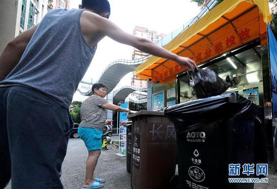"""8月5日,上海市城市花苑小区居民将垃圾""""干湿分离""""后投放到定点垃圾房。新华社记者 陈飞 摄"""